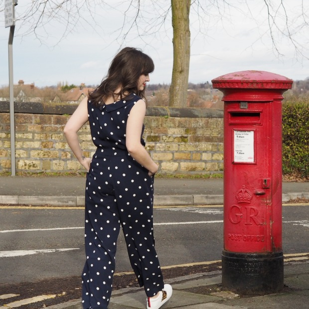 Clarissa navy spot jumpsuit by Boden, styled with trainers next to a red postbox